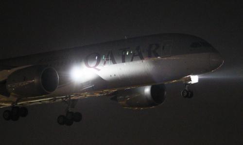 Lądowanie Dreamlinera Katarskich Linii Lotniczych Qatar Airways nocą.